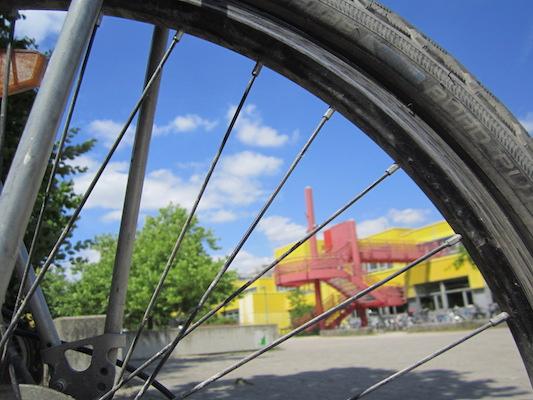 ! Sophie Kelch - Durch Gegenstaende fotografieren (Schulgebaeude durch Fahrradspeiche)